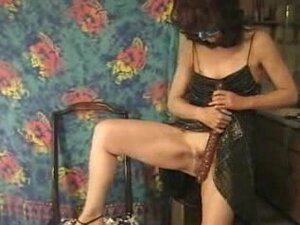 Masked mature shoves a long red toy inside her