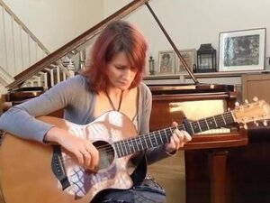 Redhead playing guitar down blouse and cleavage,