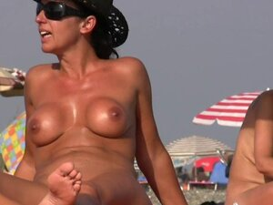 Nudist on the beach with big boobs is taking a